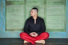 Retrato de um homem novo, de uma camisa preta e de umas folgas vermelhas fotos de stock