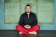 Retrato de um homem novo, de uma camisa preta e de umas folgas vermelhas fotografia de stock royalty free