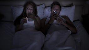 Retrato de um homem novo e de sua esposa ambos que usam seus smartphones ao encontrar-se junto na cama vídeos de arquivo