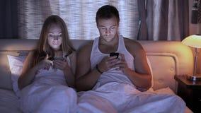 Retrato de um homem novo e de sua esposa ambos que usam seus smartphones ao encontrar-se junto na cama filme