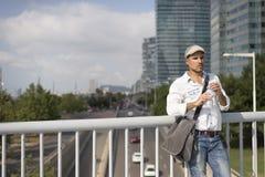 Retrato de um homem novo e masculino que bebe uma água fora imagens de stock