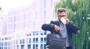 Retrato de um homem novo em um revestimento com uma barba e vidros que anda abaixo do café bebendo da rua e que olha fotografia de stock royalty free