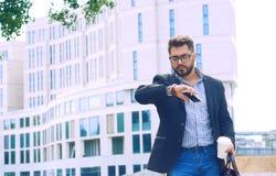 Retrato de um homem novo em um revestimento com uma barba e vidros que anda abaixo do café bebendo da rua e que olha imagens de stock