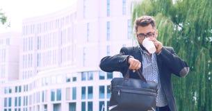 Retrato de um homem novo em um revestimento com uma barba e vidros que anda abaixo do café bebendo da rua e que olha foto de stock royalty free