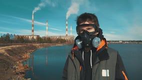 Retrato de um homem novo em uma máscara do respirador ou de gás No fundo o fumo vem das tubulações de um hidroelétrico filme