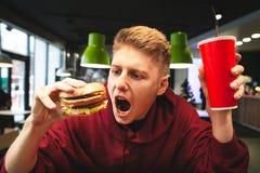 Retrato de um homem novo emocional que guarda um vidro da bebida e de um hamburguer, olhando um hamburguer e indo morder fotografia de stock