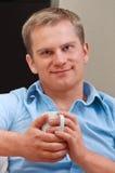 Retrato de um homem novo feliz com copo fotografia de stock royalty free