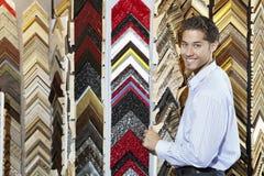 Retrato de um homem novo feliz com multi quadros coloridos no fundo Fotos de Stock Royalty Free