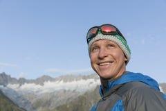 Retrato de um homem novo feliz nas montanhas de Suíça Imagens de Stock