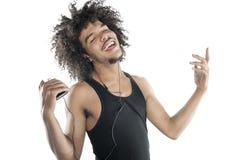 Retrato de um homem novo feliz que gesticula ao escutar o leitor de mp3 sobre o fundo branco Fotos de Stock Royalty Free