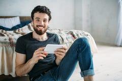 Retrato de um homem novo feliz que relaxa e que olha um programa televisivo em um tablet pc foto de stock