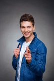Retrato de um homem novo feliz que sorri no fundo cinzento Imagens de Stock Royalty Free