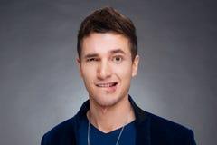 Retrato de um homem novo feliz que sorri no fundo cinzento Imagem de Stock Royalty Free