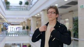 Retrato de um homem novo moderno nos vidros e no casaco de cabedal em um shopping vídeos de arquivo