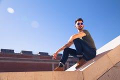 Retrato de um homem novo na moda em um dia ensolarado na cidade Imagem de Stock
