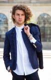 Retrato de um homem novo na moda na cidade que olha afastado Fotografia de Stock Royalty Free