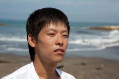 Retrato de um homem novo na praia fotografia de stock royalty free