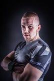 Retrato de um homem novo no equipamento do esporte no estúdio da aptidão contra o fundo escuro Foto de Stock