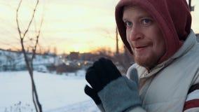 Retrato de um homem novo que está congelado contra uma arquitetura da cidade no inverno filme