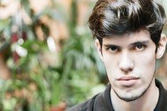 Retrato de um homem novo que olha a câmera, pensamento, sério fotos de stock royalty free