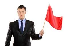 Retrato de um homem novo que prende uma bandeira vermelha Fotografia de Stock Royalty Free