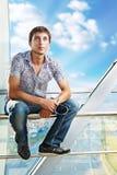 Retrato de um homem novo que senta-se nos trilhos Imagem de Stock Royalty Free