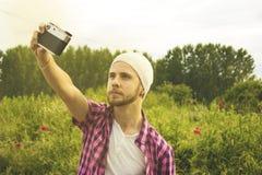 Retrato de um homem novo que toma um selfie Imagem de Stock Royalty Free