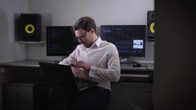 Retrato de um homem novo que trabalha no portátil e que ajusta seu dispositivo com smartwatch em sua mão Colaborador do contempor filme
