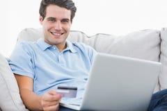 Retrato de um homem que usa seu cartão de crédito para comprar em linha Fotografia de Stock Royalty Free