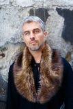 Retrato de um homem 'sexy' na pele do lobo e da expressão pensativa em sua cara, uma parede da estrutura no fundo imagens de stock