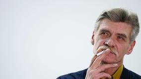 Retrato de um homem superior com um cigarro e da fala no fundo branco video estoque