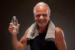 Retrato de um homem superior de sorriso com uma toalha e uma garrafa de água Foto de Stock