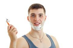 Retrato de um indivíduo de sorriso novo com espuma em sua cara que olha reta e guardando uma lâmina Imagens de Stock