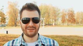 Retrato de um indivíduo farpado de sorriso nos óculos de sol e na camisa vídeos de arquivo