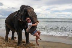 Retrato de um indivíduo novo com um elefante no fundo de uma praia tropical do oceano fotografia de stock