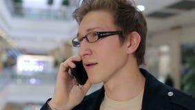 Retrato de um indivíduo novo elegante com vidros em um shopping com telefone vídeos de arquivo