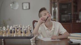 Retrato de um indivíduo pensativo bonito que senta-se na tabela e que escreve algo em um pedaço de papel filme