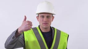 Retrato de um indivíduo seguro em um uniforme do construtor com um capacete branco em seu polegar principal da exibição isolado a video estoque