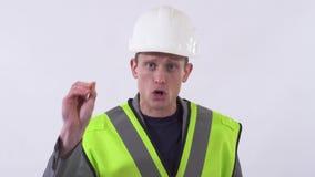 Retrato de um indivíduo seguro em um uniforme do construtor e do capacete branco em sua cabeça que fala à câmera que dá o conselh video estoque