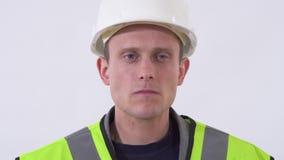 Retrato de um indivíduo smilling seguro em um uniforme do construtor com e em um capacete Tiro no estúdio em um fundo branco filme