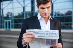 Retrato de um jornal considerável da leitura do homem de negócios fora foto de stock