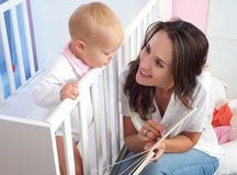 Retrato de um livro de leitura bonito da mãe ao bebê bonito Fotos de Stock