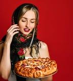 Retrato de um louro bonito novo no lenço que guarda uma torta caseiro deliciosa da cereja fotos de stock