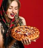 Retrato de um louro bonito novo no lenço que guarda uma torta caseiro deliciosa da cereja imagem de stock