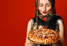 Retrato de um louro bonito novo no lenço que guarda uma torta caseiro deliciosa da cereja fotografia de stock royalty free
