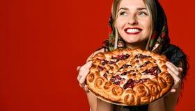 Retrato de um louro bonito novo no lenço que guarda uma torta caseiro deliciosa da cereja foto de stock royalty free