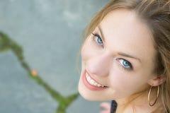 Retrato de um louro da jovem mulher com os olhos azuis que olham acima, sorriso toothy fotos de stock royalty free