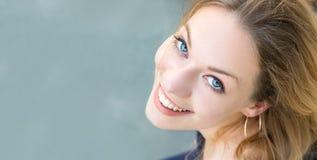 Retrato de um louro da jovem mulher com os olhos azuis que olham acima, sorriso toothy fotos de stock