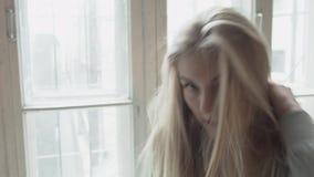 Retrato de um louro feliz que anda à janela e ao sorriso Jovem mulher bonita sobre contra uma janela que olha filme