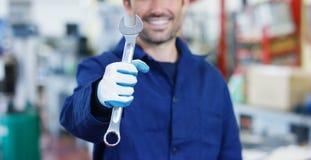 Retrato de um mecânico de carro bonito novo em uma oficina de reparações do carro, mãos com uma chave inglesa Conceito: reparo da Imagens de Stock Royalty Free